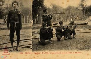 Description: Đội trưởng Nghĩa quân và những người lính luyện tập bắn súng.
